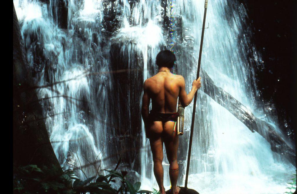 Ein Penan steht mit dem Rücken zur Kamera im Urwald von Sarawak vor einem Wasserfall. In der rechten Hand hält er einen Speer.